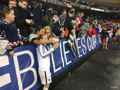 French player takes a selfie with fans at RFK Stadium in Washington after France defeated the USA, 3-0, to win the SheBelieves Cup. (Photo: P. Brewer / VOA)