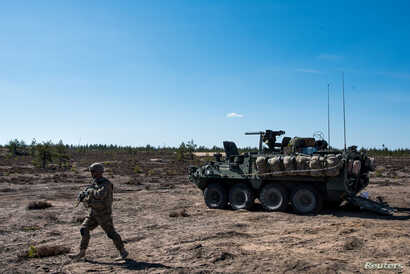"""A US army soldier and Stryker armored vehicle take part in the """"Arrow 16"""" exercise with the Finnish Army in Niinisalo, Finland, May 4, 2016. U.S. troops are using the Stryker vehicle while offering support near Manbij, Syria, March 6, 2017."""