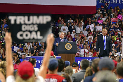 Republican Senate candidate, current West Virginia Attorney General Patrick Morrisey, speaks as President Donald Trump listens during a rally, Aug. 21, 2018, at the Civic Center in Charleston W.Va.