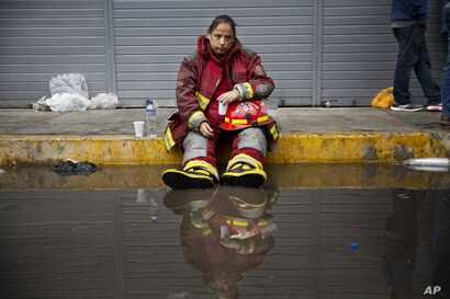 Exhausted firefighter Julia Alegre Smith rests after working to battle a warehouse fire in Lima, Peru, June 23, 2017.