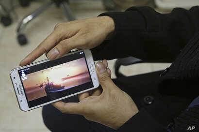 "Farhad Azima, Iranian director and screenwriter of the animated film, ""Battle of the Persian Gulf II,"" shows a clip from the movie on his cellphone at his office in Tehran, Iran, Feb. 26, 2017."