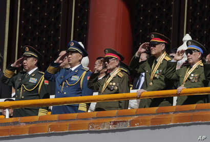 Chinese military officials salute during a parade commemorating the 70th anniversary of Japan's surrender during World War II held in front of Tiananmen Gate, in Beijing, Thursday, Sept. 3, 2015.