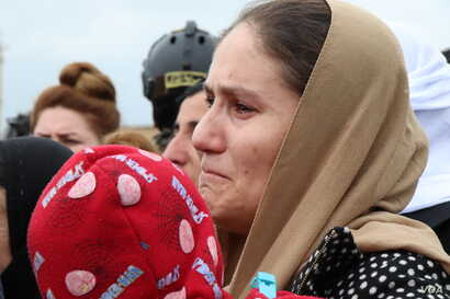 Women and men cry as they watch the U.N. team begin their search for the remains of thousands of victims in Kocho, Iraq, March 15, 2019.