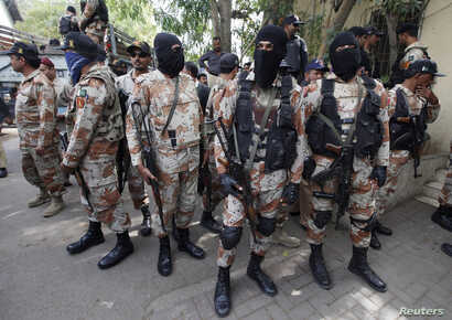 Paramilitary soldiers stand guard, as they present men (unseen), who were detained during Wednesday's raid on the Muttahida Qaumi Movement political party headquarters, before an anti-terrorism court in Karachi, March 13, 2015.