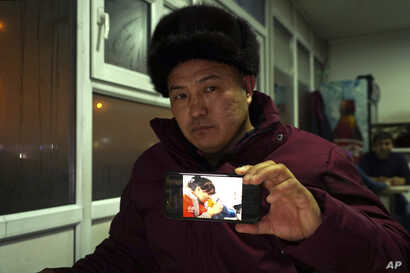 """In this Dec. 9, 2018, photo, Orynbek Koksebek, a former detainee in a Chinese internment camp, holds up a phone showing a state television report about what Beijing calls """"vocational training centers"""" for a photo in a restaurant in Almaty, Kazakhstan..."""