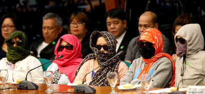 Family members of alleged drug pushers who were killed during a meth raid wear masks during a Senate hearing regarding a crackdown on illegal drugs in Pasay, Metro Manila, Philippines, Aug. 23, 2016.