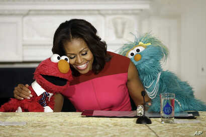First lady Michelle Obama, center, with PBS Sesame Street's characters Elmo, left, and Rosita, right, as they help promote fresh fruit and vegetable consumption to kids in an event in the State Dining Room of the White House in Washington, Wednesday,...