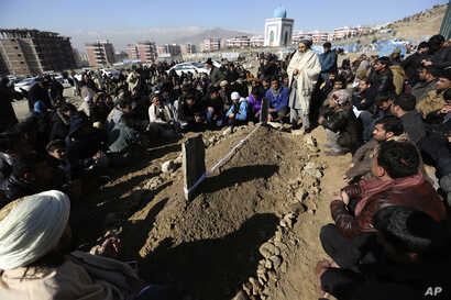 Villagers pray in front of the grave of a victim of Tuesday's two bombings in Kabul, Afghanistan, Jan. 11, 2017.