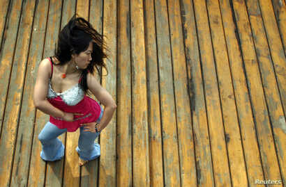 Chinese internet star Furong Jiejie, aka Sister Furong, dances on a roof in Beijing, Aug. 10, 2005.