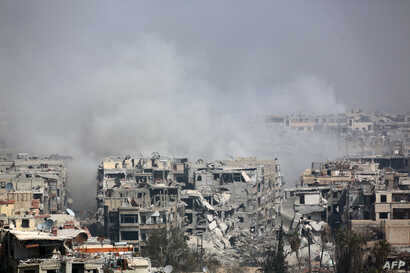 Smoke billows following Syrian government bombardment on the rebel-held besieged town of Harasta, in the Eastern Ghouta region on the outskirts of Damascus, March 12, 2018.