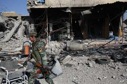 FILE- A Kurdish fighter walks past a destroyed building in the town of Sinjar, after they took it from the Islamic State group in a joint operation with the coalition forces, Nov. 13, 2015.