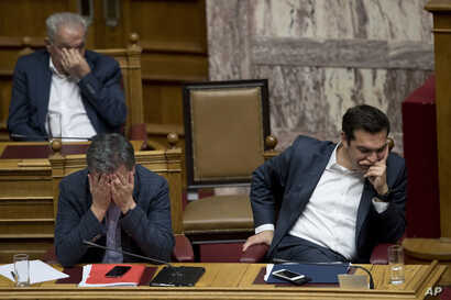 Greek Finance Minister Euclid Tsakalotos, left, and Greece's Prime Minister Alexis Tsipras, right, react during a parliamentary session to vote more austerity measures as part of an agreement with international bailout creditors, in Athens, May 18, 2...
