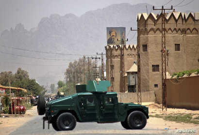 Afghan policemen stand guard near the house of the cousin of Afghan President Hamid Karzai, Hashmat Karzai, at the site of a suicide attack in Kandahar July 29, 2014. Afghan President Hamid Karzai's powerful cousin Hashmat, a close ally of presidenti...