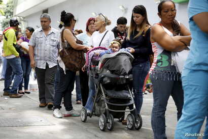 A mother takes care of her daughter while queuing in a line outside a drugstore to buy diapers in Caracas, Venezuela, July 21, 2015.
