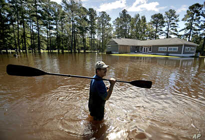The home of Kenny Babb is surrounded by water as he retrieves a paddle that floated away while the Little River continues to rise in the aftermath of Hurricane Florence in Linden, North Carolina, Sept. 18, 2018.