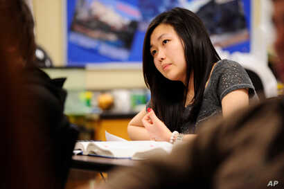FILE - Sally Kim takes notes during a physics class at Columbia Independent School in Columbia, Mo. Kim's parents, who live in South Korea, sent her to live with relatives in Columbia for a better education that provides more collegiate opportunities...