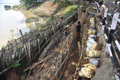 Indian laborers work to build up a river bank after flood waters and incessant rain eroded away the edges of the River Brahmaputra in Guwahati, June 15, 2017.