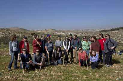 American rabbinical students take a group photo,  with the village of Attuwani in the background, during a day planting olive trees, near Hebron in the West Bank, Jan. 25, 2019.