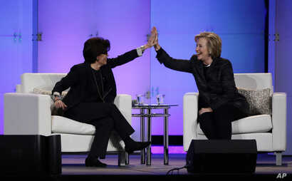 FILE - Hillary Rodham Clinton, right, and technology commentator Kara Swisher high-five during a keynote address at the Watermark Silicon Valley Conference for Women.
