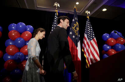 Democratic candidate for 6th congressional district Jon Ossoff, right, steps onstage with his fiancee Alisha Kramer to announce he conceded to Republican Karen Handel at his election night gathering in Atlanta, Georgia, June 20, 2017.