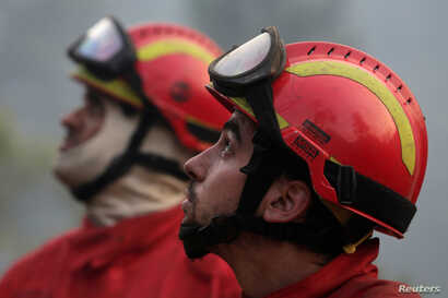 Firefighters take a break to watch planes dump water on a forest fire in Mendeira, Portugal, June 19, 2017.