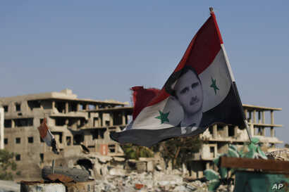 In this Sunday, July 15, 2018, photo, a Syrian national flag with the picture of President Bashar Assad hangs at an Army check point, in the town of Douma in the eastern Ghouta region, near the Syrian capital Damascus, Syria.