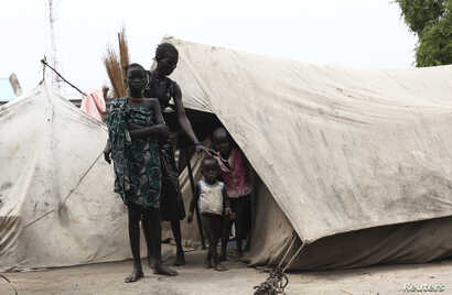 A woman from the Murle tribe and her children stand outside their tent in Pibor town in Jonglei state, South Sudan, July 18, 2013.
