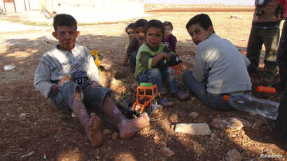 Syrian children, including a boy (L) injured during clashes between the Syrian Army and rebels, play with toys on the Syrian side of the border with Turkey, near Idlib, after having fled the violence in their town, October 13