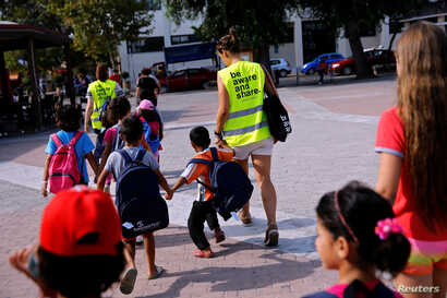 """Volunteers escort refugee children at the volunteer-run """"Refugee Education Chios"""" school on the island of Chios, Greece, Sept. 7, 2016."""