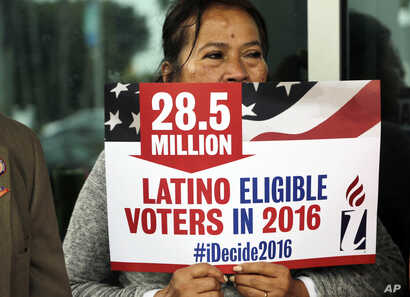 FILE - Georgina Arcienegas holds a sign in support of Latino voters during a protest outside the office of Florida Rep. Carlos Trujillo on Jan. 12, 2016, in Doral, Fla.