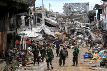 Government soldiers stand in front of damaged houses and buildings in Marawi city, Philippines, Oct. 25, 2017.