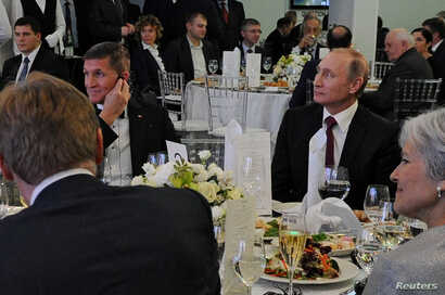 FILE - Russian President Vladimir Putin (R) sits next to retired U.S. Army Lieutenant General Michael Flynn (L) as they attend an exhibition marking the 10th anniversary of RT (Russia Today) television news channel in Moscow, Russia, Dec.10, 2015.