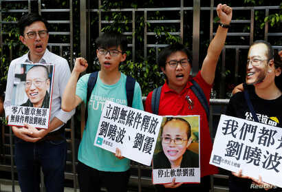 Student leader Joshua Wong, second from left, chants slogans during a protest demanding the release of Chinese Nobel rights activist Liu Xiaobo outside China's Liaison Office in Hong Kong, June 27, 2017.