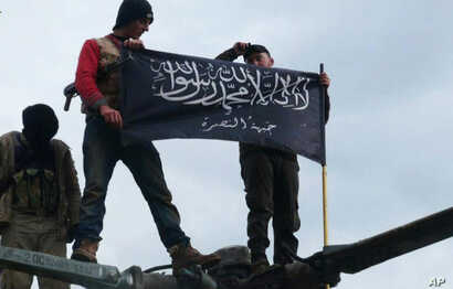 FILE - Rebels from al-Qaida-affiliated Jabhat al-Nusra, also known as the Nusra Front, wave their brigade flag, as they step on the top of a Syrian air force helicopter at Taftanaz air base, Jan. 11, 2013.