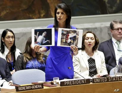 U.S. Ambassador to the United Nations Nikki Haley shows pictures of Syrian victims of chemical attacks as she addresses a meeting of the Security Council on Syria at U.N. headquarters, in New York, April 5, 2017.