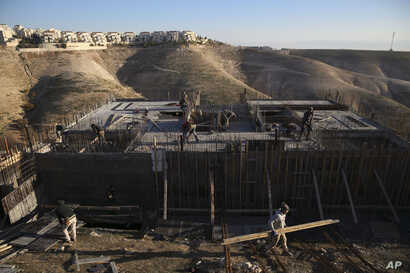 FILE - Palestinian laborers work at a construction site in a new housing project in the Israeli settlement of Maale Adumim, near Jerusalem, Feb. 7, 2017. Yaakov Katz, a prominent West Bank settler, says the rapid growth in the number of Israelis sett