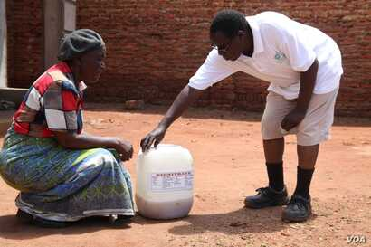 Founder of Urine for Weath Project Goodfellow Phiri buying urine from a customer in the capital, Lilongwe. (L. Masina/VOA)