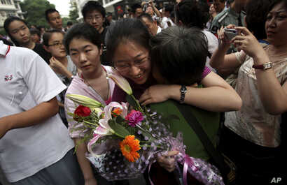 """FILE - A Chinese student is greeted by a relative after taking the annual college entrance examinations in Beijing, June 8, 2010. Each year, about 10 million high school seniors across China take the """"gaokao"""", the exam that is the sole determinant fo..."""