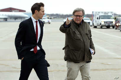 FILE - Jared Kushner, son in-law of President-elect Donald Trump, left, walks with Trump's Chief Strategist Stephen Bannon at Indianapolis International Airport, Dec. 1, 2016.