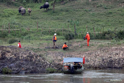 FILE - A Chinese team of geologists surveys the Mekong River banks, at the Laos side, at the border between Laos and Thailand, April 23, 2017.