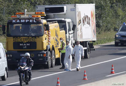 A truck in which up to 50 migrants were found dead, is prepared to be towed away on a motorway near Parndorf, Austria, Aug. 27, 2015.