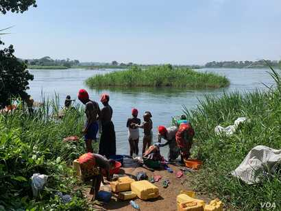 Women bathe and do laundry at the shores of Victoria Nile River, Kayunga district, Uganda.