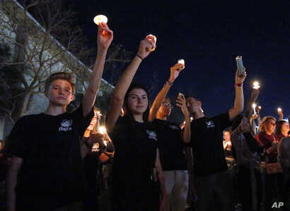 Attendees raise their candles at a candlelight vigil for the victims of the shooting at Marjory Stoneman Douglas High School, Feb. 15, 2018, in Parkland, Fla.