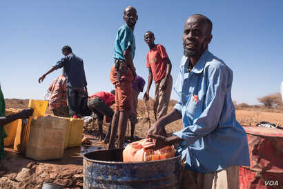 Mohamed Ibrahim Yassin scoops well water from a barrel to feed his remaining livestock in Somaliland region of Somalia, Feb. 9, 2017. (VOA/ Jason Patinkin)