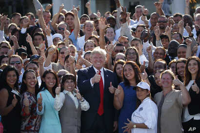 Republican presidential candidate Donald Trump poses for photographs during an campaign event with employees at Trump National Doral, Tuesday, Oct. 25, 2016, in Miami.