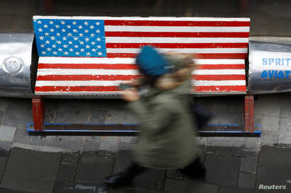 A woman walks past a bench painted in the colors of the U.S. flag, outside a clothing store in Beijing, China, Jan. 7, 2019.