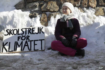 Climate activist Greta Thunberg poses for media outside the congress center where the World Economic Forum take place in Davos, Switzerland, Friday, Jan. 25, 2019. The poster reads: 'School strike for the climate'.