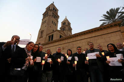FILE - Egyptians hold candles in front of the Coptic Christian Cathedral in tribute to the victims of a bomb attack inside a Coptic cathedral in Cairo, Dec. 17, 2016.