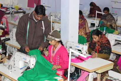 Mohammad Riyaz who set up a solar-powered garment manufacturing unit in Kamlapur village, in the Indian state of Uttar Pradesh, works with one of the 25 women who work for him stitching clothing, Jan. 9, 2018.