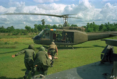 U.S. paratroopers carry a wounded man on a stretcher into a waiting helicopter in Vietnam on May 7, 1966.